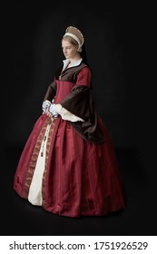 A young Tudor woman in a red and brown dress and a French hood