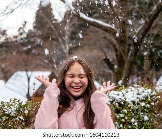 Young tween girl having fun in snow