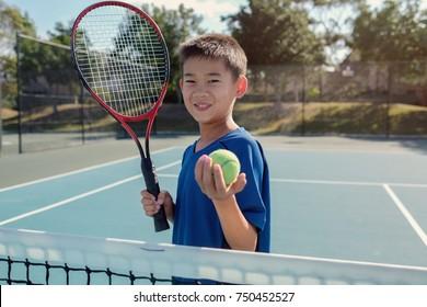 Young tween preteen Asian boy tennis player on outdoor blue court