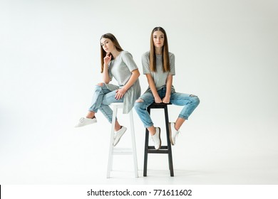 young twins in similar clothing looking at camera while sitting on chairs