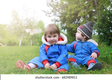 young twins sitting on a green meadow in the early spring