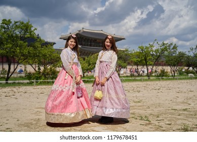 Young two cute Asian girls dressing in traditional South Korean old fashion Hanbok style standing in Gyeongbokgung Palace (Public open for tourists). Travel in Asia Landmark concept.