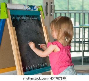 Young two year old girl drawing with chalk on blackboard and using both hands ambidextrously