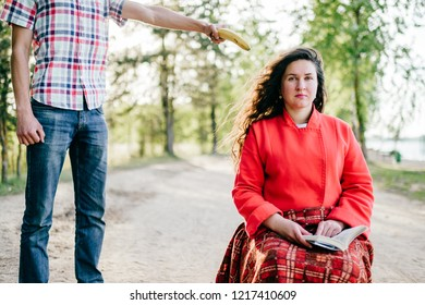 Young ugly boy threatening adult helpless female sitting in chair on road.  Odd chubby beautiful helpless woman sitting in red clothes outdoor.  Young comic strange girl with plaid cover her legs