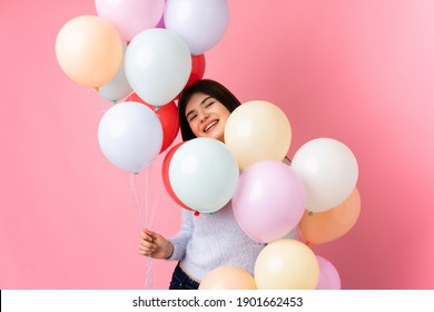 Young Ukrainian teenager girl holding lots of balloons over isolated pink background