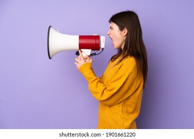 Young Ukrainian teenager girl over isolated purple background shouting through a megaphone