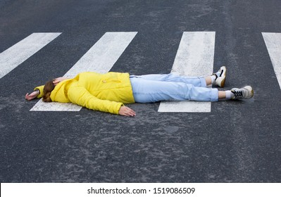 Young unconscious woman at accident scene, crash on the road. Pedestrian girl hit by a car on the road at the crosswalk while crossing. Downed female person is lying on asphalt.