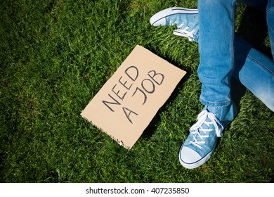 "Young unemployed man lookig for a job with ""Need a job"" cardboard"