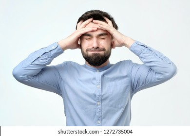 Young unhappy businessman holds his head, stress, headache and frustration concept