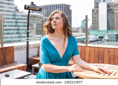 Young unhappy elegant woman looking up sitting on rooftop restaurant table in New York City NYC in blue dress with urban cityscape skyscrapers waiting for date