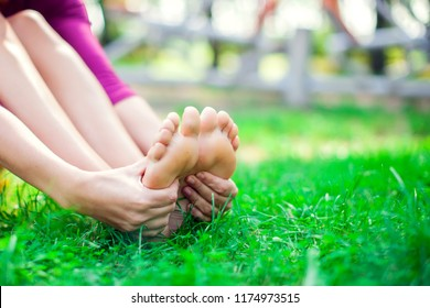 Young unhappy woman feeling pain in her foot during sport workout in the park. Sport, medicine and people concept