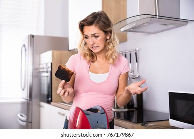 Young Unhappy Woman Removing Slices Of Burnt Toast From Toaster In Kitchen