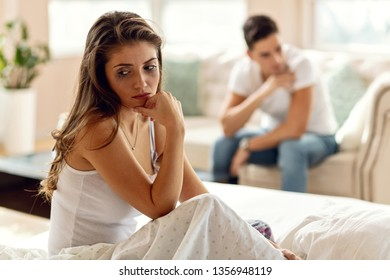 Young unhappy woman with smudged mascara thinking while having relationship difficulties with her boyfriend. The man is in the background.