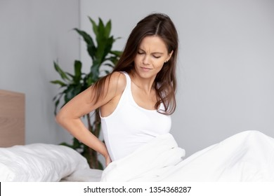 Young unhealthy female waking up sitting on bed touch sudden aching lower back, suffers morning discomfort back pain. Bad mattress, incorrect posture, painful periods severe menstrual cramps concept