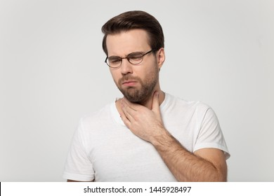 Young unhealthy guy in glasses coughing has sore throat loss of voice after loud screaming isolated on gray studio background, man touch neck feels discomfort painful feelings hard to swallow concept