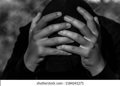 Young unidentifiable teenage boy  holding hes head at the correctional institute in black and white, conceptual image of juvenile delinquency, focus on the boys hand.