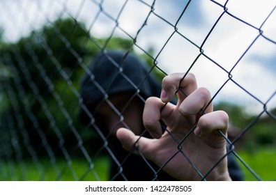 Young unidentifiable teenage boy holding the wired garden at the correctional institute, conceptual image of juvenile delinquency, focus on the boys hand.