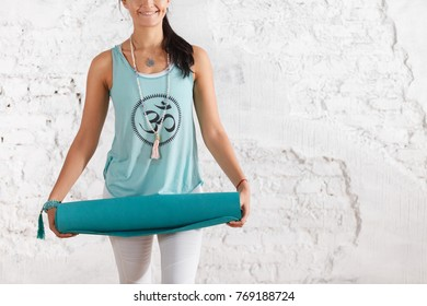 Young unidentified positive young brunette woman holding  rug for practicing gymnastics in the gym