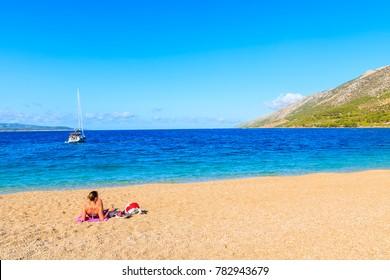 Young unidentified woman tourist sunbathing on Zlatni Rat beach (Golden Horn) with beautiful sea water, most famous beach of Adriatic Sea, Brac island, Croatia