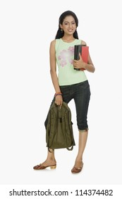 Young university student carrying a bag and books