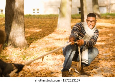 Young university student playing tug of war on college campus