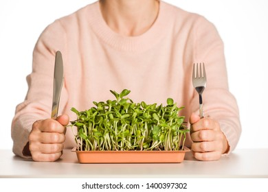 Young unknown woman with fork and knife and fresh homegrown sunflower microgreens in plastic coucer on white background