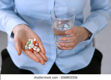 Young unknown woman holding pills and glass of water, closeup of hands.  Medicine and healthcare concept