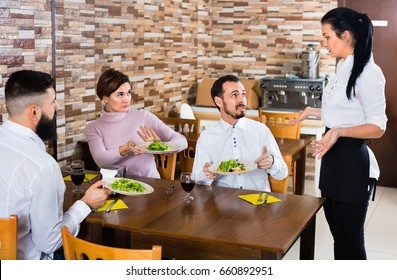 Young unpleased  angry ordinary couple doesn't like the service and food at cafe