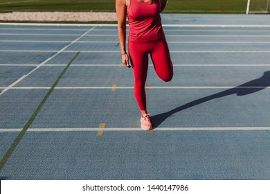 young unrecognizable fitness woman runner stretching legs on stadium blue track at sunset. Sport and healthy lifestyle concept
