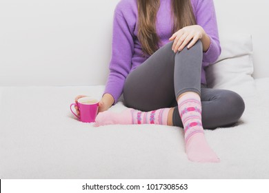 Young unrecognizable woman at home in bed sitting, wearing winter loungewear and holding a cup of coffee