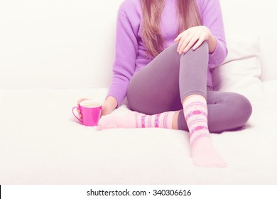 Young unrecognizable woman sitting in bed at home with coffee or tea cup. Teenage girl relaxing holding hot beverage mug, wearing winter loungewear. Medium retouch, pastel filter.