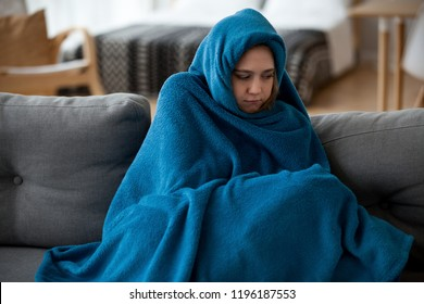 Young unsatisfied sick woman covered with warm blue blanket plaid from head to toes sitting alone on couch in living room at cold home. Seasonal problems, virus diseases and central heating concept - Shutterstock ID 1196187553