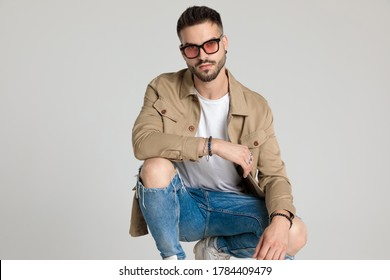 young unshaved casual model in jacket wearing sunglasses, holding elbows on knees and crouching on grey background