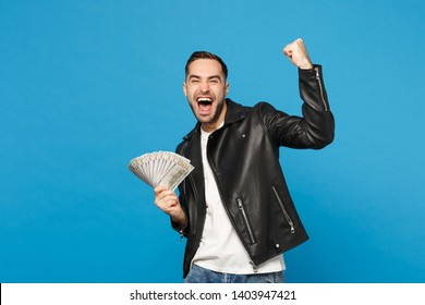 Young unshaven man in black leather jacket white t-shirt holding fan of cash money in dollar banknotes isolated on blue wall background studio portrait. People lifestyle concept. Mock up copy space