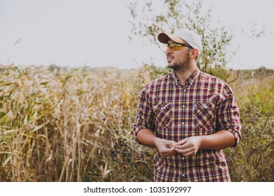 Young unshaven man in checkered shirt, cap and sunglasses looking away holds maggot bait for fishing against the background of shrubs and reeds on a sunny day. Lifestyle, recreation, leisure concept.