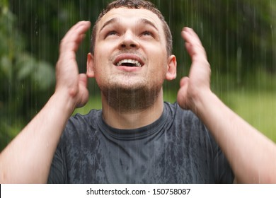 Young unshaven man getting wet under the rain.