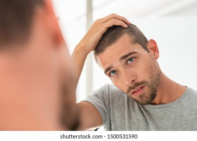 Young unshaven man looking at mirror in bathroom at home. Handsome guy looking at his face in mirror, checking hair and hairline. Man in pijamas concerned with hair loss.