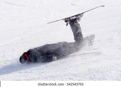 young unskilled man falling on cold snow in ski crash at Sierra Nevada resort in Spain in winter sport accident concept