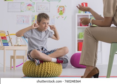 Young upset boy covering ears during therapy session with child psychologist