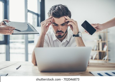 Young upset businessman is working in modern light office under stress. Feel of tiredness.