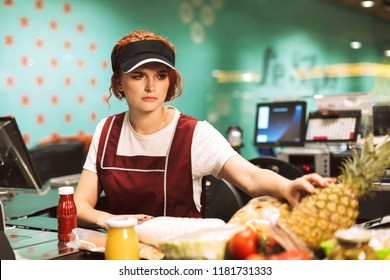 Young upset female cashier in uniform thoughtfully looking on products working in modern supermarket