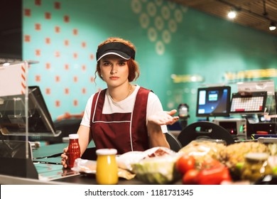 Young upset female cashier in uniform thoughtfully looking in camera working in modern supermarket