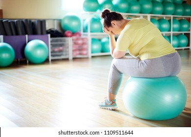 Young upset oversized woman in sportswear sitting on fitball expressing despair or tiredness
