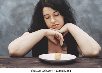 Young upset overweight woman bored of diet restricts looking at sweet cake. Dieting, healthy food, weight loss, sugar addiction