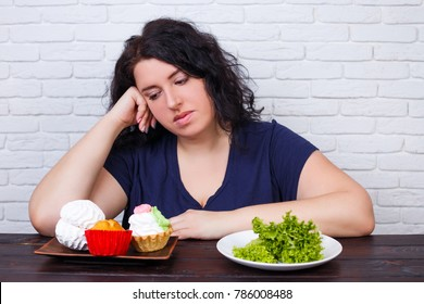 Young upset overweight woman bored of diets choosing between healthy and junk food. Dieting, healthy food, weight losing, slimming