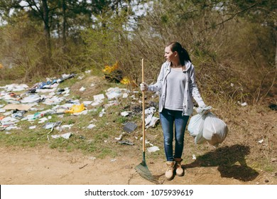 Young upset shocked woman cleaning holding trash bags and rake for garbage collection in littered park. Problem of environmental pollution. Stop nature garbage, environment protection concept