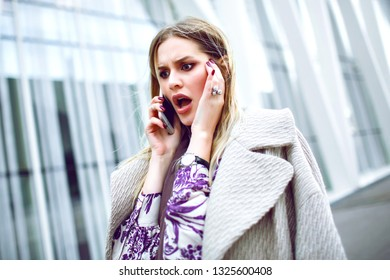 Young upset surprised woman making call by her smartphone, shocked emotions, elegant business lady outfit, toned colors, spring autumn mid season.