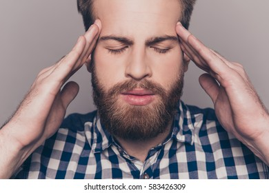 Young upset tired man having migraine and touching head