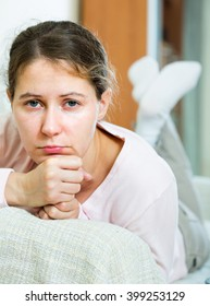 Young upset woman sitting in domestic interior with headache