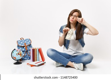 Young upset woman student crying holding dollar bills feeling stressed by lack of money sit near globe, backpack school books isolated on white background. Education in high school university college